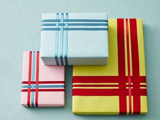 For gifts that need to be shipped or stacked flat, weave differently sized and colored ribbons in a simple pattern – crossing one ribbon over another – and attaching in back. Or use washi tape, which comes in so many colors and holiday-themed patterns.