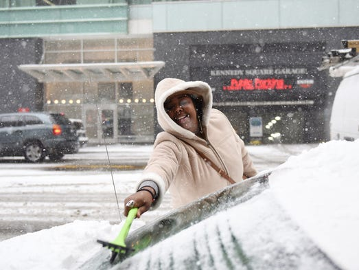 Haleema Russell cleans the snow off her car in Detroit.