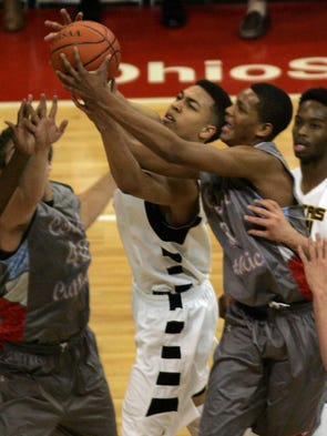 Roger Bacon's Fred Moore battles Lima Central Catholic's Dantez Walton and  Jake Williams for a rebound.