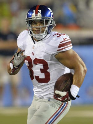 New York Giants running back Peyton Hillis (33) rushes against the Buffalo Bills during the Pro Football Hall of Fame exhibition NFL football game Sunday, Aug. 3, 2014, in Canton, Ohio. New York won 17-13.