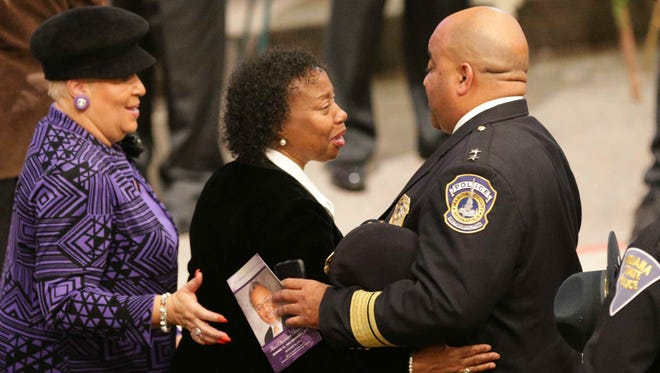 Indianapolis Police Chief Rick Hite (right) gives his condolences to Quinetta Brown (center) at the funeral of her husband, Indianapolis radio host Amos Brown, on Saturday, Nov. 14, 2015, at Light of the World Christian Church in Indianapolis.