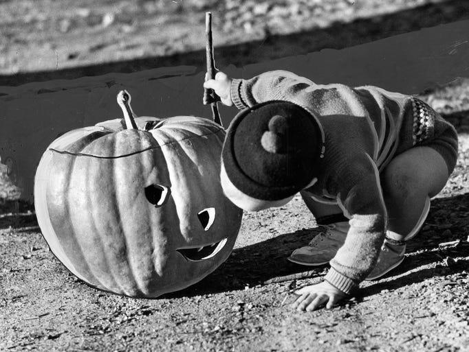 A little boy inspects a jack-o'-lantern  in 1938. The