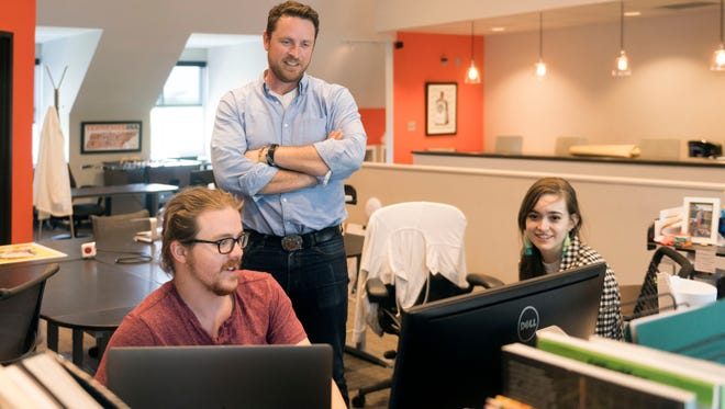 Designsensory creative director Chris McAdoo with UX Architect Kaleigh Veca, right, and graphic designer Ben Maxey.