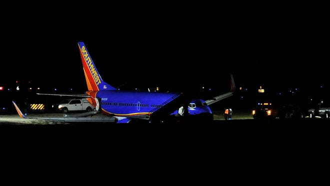 Southwest Flight 31 rests off taxiway T4 near the terminal. The plane went off the taxiway and into the grass, getting stuck in a ditch at the Nashville International Airport Tuesday, Dec. 15, 2015 in Nashville, Tenn.