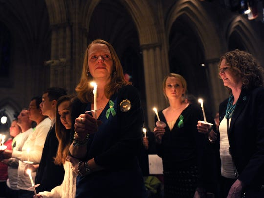 Miranda Pacchiana (center), of Newtown, Conn. holds a candle at the conclusion of a National Vigil for Victims of Gun Violence just prior to the first anniversary marking the Sandy Hook Elementary School mass shooting at Washington National Cathedral on December 12, 2013.