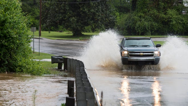 A truck drives through pooling water on Concord St. on Sunday, April 23, 2017.