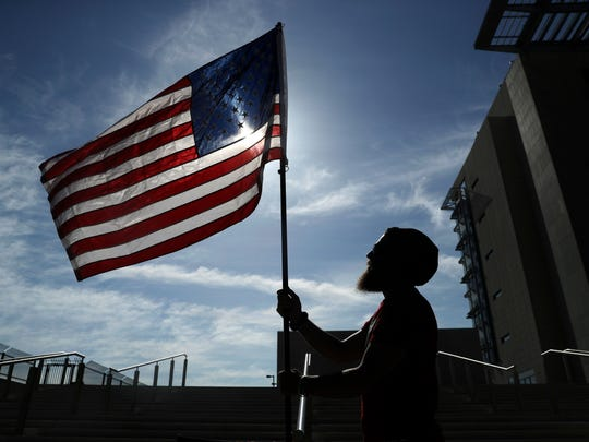 A protester holds up a flag outside of a federal courthouse, on April 10, 2017, in Las Vegas. The protester and others stood outside the courthouse in support of six defendants accused of wielding weapons against federal agents during a 2014 standoff involving cattleman and states' rights advocate Cliven Bundy.