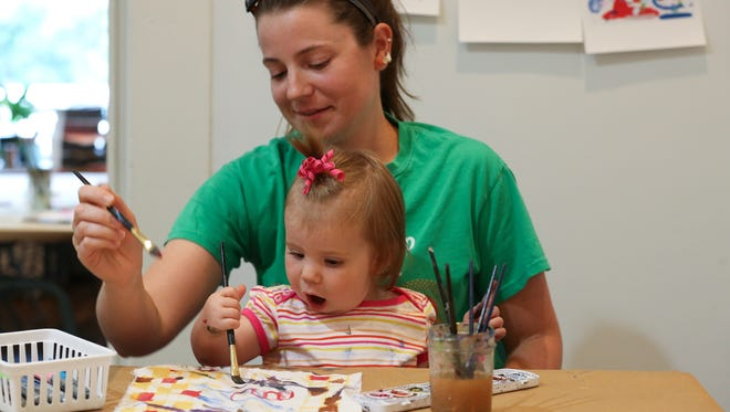 Amy Frazier watched as her daughter Coraline Earhart, 1, was captivated as she painted a peace flag during the Crafting for Kindness event on Frankfort Ave.July 31, 2016