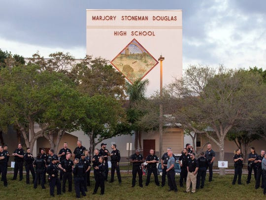 Law enforcement agents line up as students head back to school at Marjory Stoneman Douglas High School on Feb. 28, 2018, in Parkland, Fla.