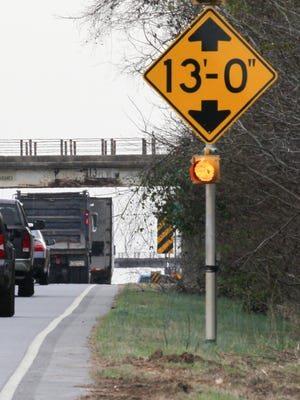 A truck drives in the South bound lane, by a warning sign for a bridge 13-feet over U.S. 29 earlier this year, outside Williamston in Anderson County.