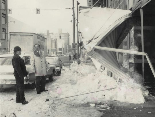 Two men inspect a damaged marque outside of Wilson's