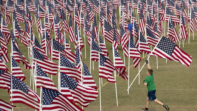 Nathanael Garlow, 10, sets up a display at the 4th annual Field of Honor at San Gabriel Park in Georgetown on Friday. The display of 1,200 American flags honors veterans, first responders and medical workers.