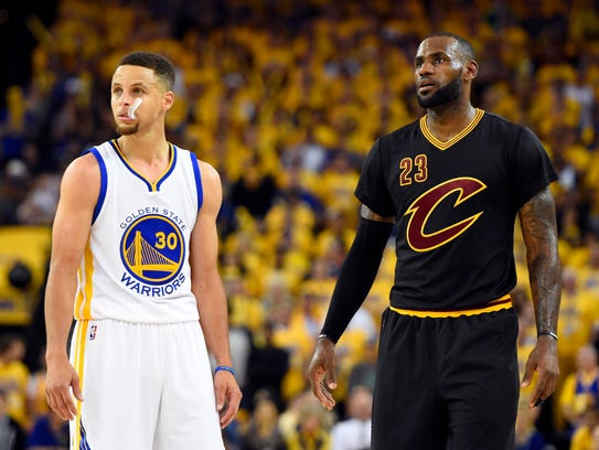 LeBron James and Stephen Curry look on during the third