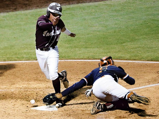 Rudy Gutierrez—El Paso Times Victor Gonzalez, left, of Ysleta lands on home plate to score as Riverside catcher Cesar Garcia just misses the throw Tuesday night at Southwest University Park.