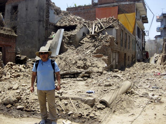 Dr. Sonam Ruit stands in front of some of the destruction in Nepal last month.