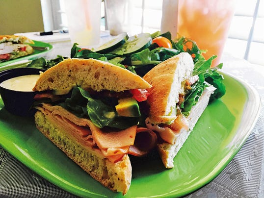 New Mexico Turkey sandwich (8.99) is topped with roasted turkey with Swiss cheese, New Mexico green chile aioli, avocado with lettuce and tomato. Sandwiches come with a side of a garden salad, caesar salad, cold quinoa fruit salad or chips.