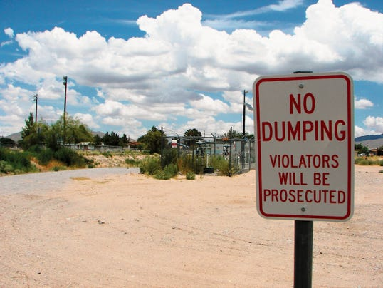 A sign warning against illegal dumping stands at the edge of the park in Anthony, near the parking area.