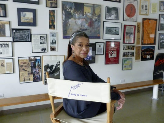 Judy Williams Henry poses in her Movement Laboratory studio, which is filled with photos, newspaper clippings and other mementos of former students.