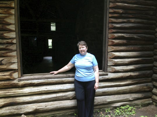 """Lebanon County Commissioner Jo Ellen Litz stands outside the Bordner Cabin in Swatara State Park. She calls the hand-built structure """"our Fallingwater,"""" a reference to Frank Lloyd Wright's architectural masterpiece in the western part of the state."""