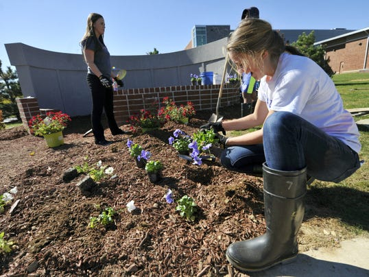 Colby Wildasin, a senior at Spring Grove Area High School, helps plant flowers in front of the Veterans' Memorial Garden the school is building on Friday. The garden honors Spring Grove graduates who have died in service, either in the military or as first responders.