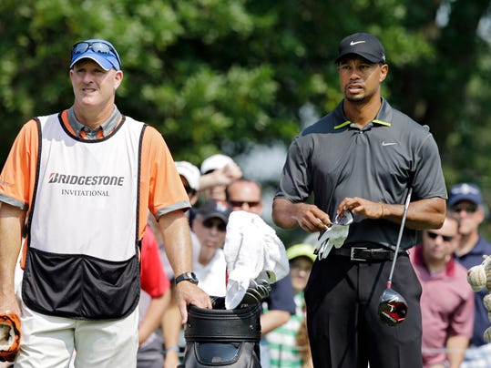 Tiger Woods waits on the 14th tee with caddie Joe Lacava, left, during the second round of the Bridgestone Invitational golf tournament Friday, Aug. 1, 2014, at Firestone Country Club in Akron, Ohio. (AP Photo/Mark Duncan)