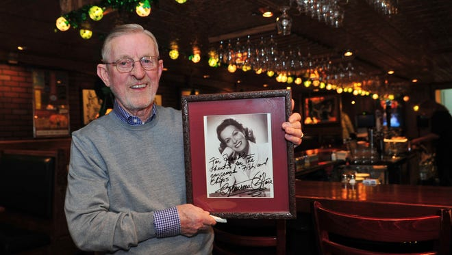 The Quiet Man owner Frank Burke, in 2015, with a picture of Maureen O'Hara, who starred in the movie for which the pub is named. She visited the pub twice.
