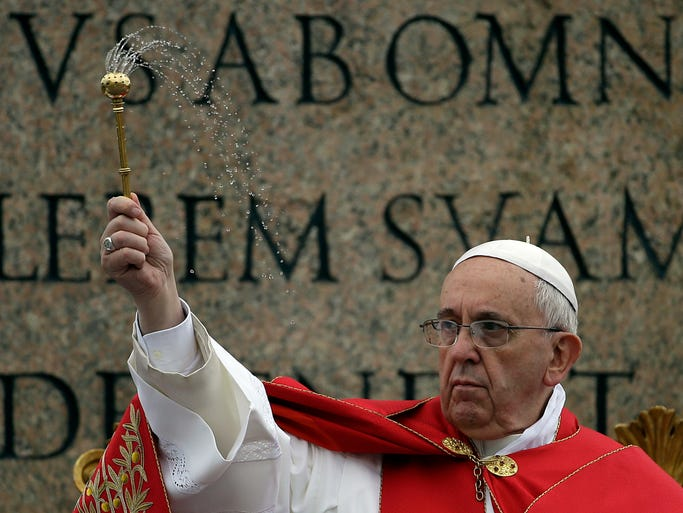 Pope Francis sprinkles holy water as he celebrates a Palm Sunday Mass in St. Peter's Square at the Vatican.