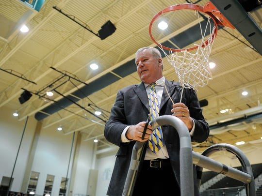 Castle's head coach Brian Gibson cuts down a piece of the net after the Class 4A North Sectional championship game against Reitz at North High School, Saturday, March, 4. 2017. Castle beat Reitz 89-69.