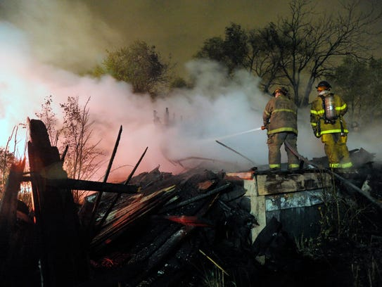 Detroit fire fighters put out hot spots at an abandoned