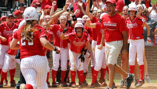 UL Softball Coach Michael Lotief leaps into the air as he and players watch Kelsey Vincent (28) head for home plate after her three-run home run against Texas during an NCAA Regional softball tournament game last season.