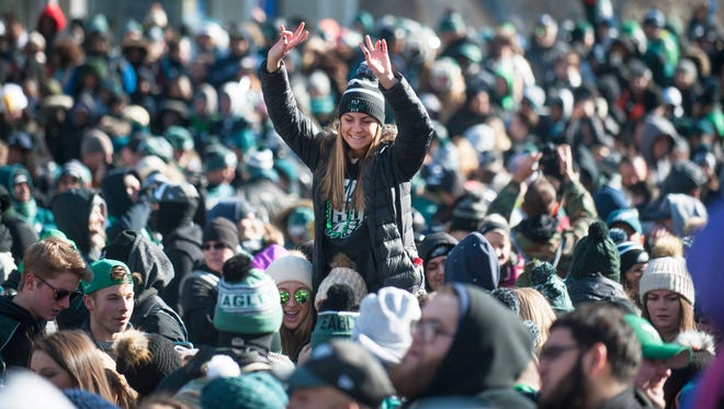 An Eagles fan is lifted above a crowd on 15th Street near John F.Kennedy Blvd. prior to the  PhiladelphiaEagles Super BowlLIIvictory parade in Philadelphia on Thursday morning.