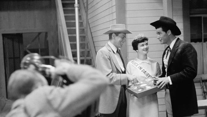 James Garner, right, accepts a box of cheese from Alice in Dairyland Nancy Trewyn on the set of the TV show Maverick in 1958.