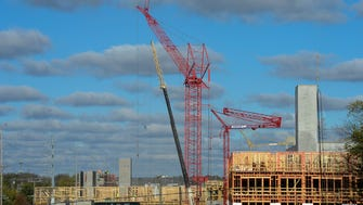 Cranes and workers strive to meet their schedule of completion of the LC Germantown apartments.