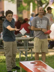 Jeff Noble and grandson Hunter Noble play cornhole.