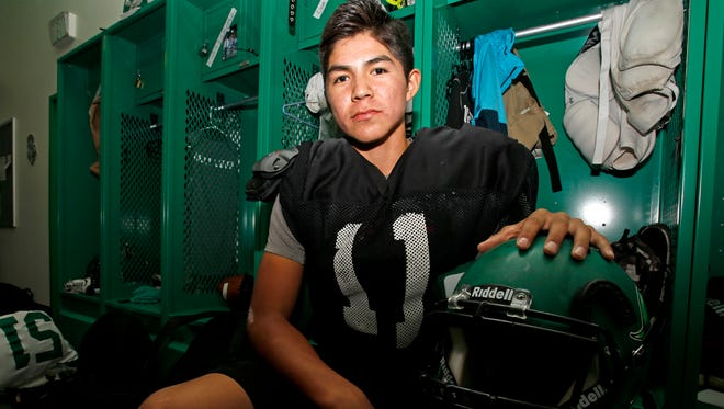 Junior quarterback Kody Becenti sits for a photo on Monday in the football locker room at Hutchison Stadium in Farmington.