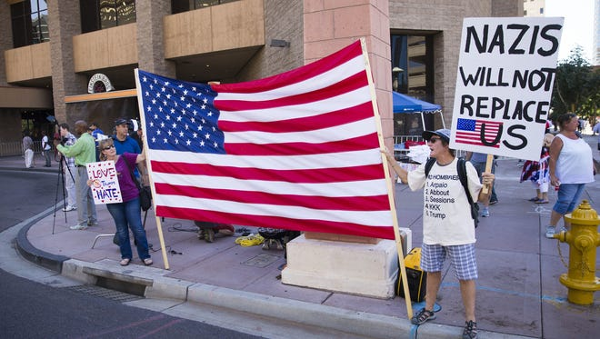 Protesters hold signs outside the Phoenix Convention Center, Aug. 22, 2017, where President Trump will hold a rally in the evening.