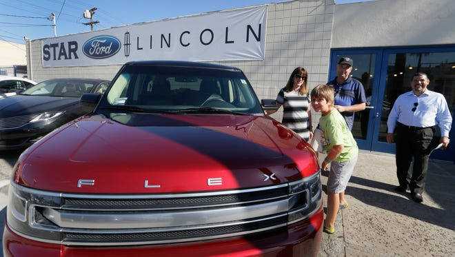 Robert Schemer, his wife, Kelly, and their son Graham, pose next to their newly purchased pre-owned 2013 Ford Flex Limited, at the Star Ford Lincoln dealership in Glendale, Calif. in July 2015. At right is sales consultant Allan Calix.