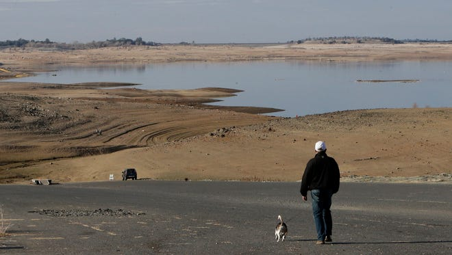 A visitor to Folsom Lake in the Sierra foothills northeast of Sacramento, Calif., walks his dog down a boat ramp that is now several hundred yards away from the waters' edge.