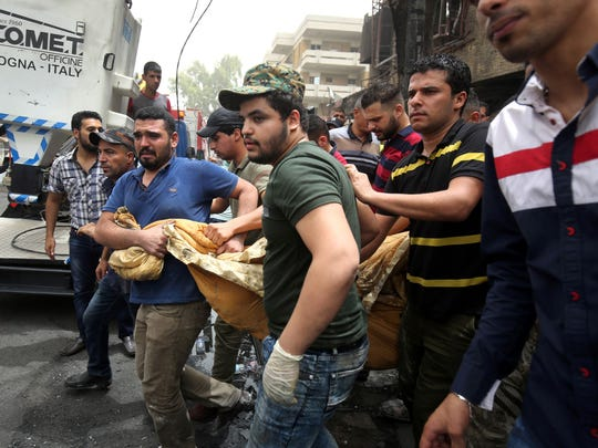 On July 4, 2016, Iraqi men carry the body of a victim