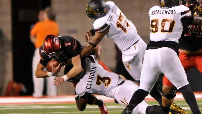 Quarterback Travis Wilson of the Utah Utes is sacked in the first quarter by DJ Calhoun (3) and Ismael Murphy-Richardson (17) of the Arizona State Sun Devils in their game at Rice-Eccles Stadium on October 17, 2015, in Salt Lake City.