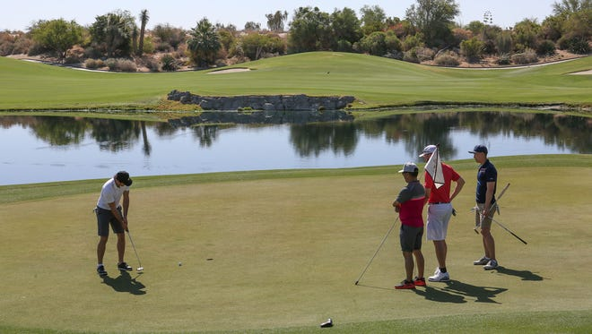 A group of golfers from Vancouver, Canada putt out on the ninth hole of the Firecliff course at Desert Willow Golf Resort in Palm Desert, May 14, 2018.