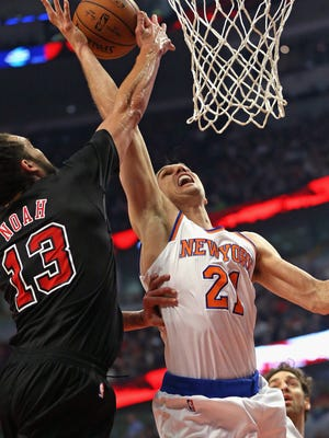 Joakim Noah #13 of the Chicago Bulls blocks a shot by Lou Amundson #21 of the New York Knicks at the United Center on March 28, 2015 in Chicago, Illinois.