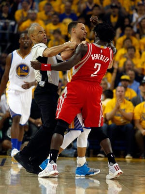 Golden State Warriors guard Stephen Curry (C) and Houston Rockets guard Patrick Beverley (R) skirmish as referee Dan Crawford (L) tries to separate them  during the first half of Game One First Round of the NBA Western Conference playoffs at Oracle Arena in Oakland.