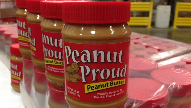 A jar of Peanut Proud peanut butter sits among 4,000 jars of peanut butter donated to the Montgomery Area Food Bank from the Alabama Peanut Producers Association.