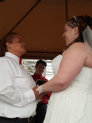Leida Torres and Chrissy Slonaker Torres exchange vows under an outdoor tent at the West Manchester Township Walmart. The two met at the store as co-workers.