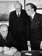 In this Jan. 2, 1939 file photo, the old family bible Frank Murphy used in taking his oath of office in the president's study in the White House is autographed by President Franklin Roosevelt immediately after ceremony. Watching are Homer Cummings, center, retiring attorney general, and Murphy, right, the new attorney general.