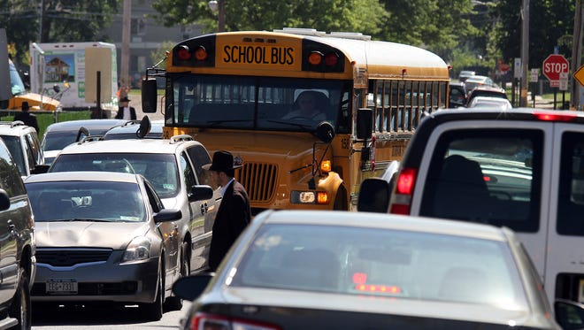 A school bus navigates through the traffic along 9th Street in Lakewood outside the Lakewood Cheder School Friday morning, June 6, 2014.