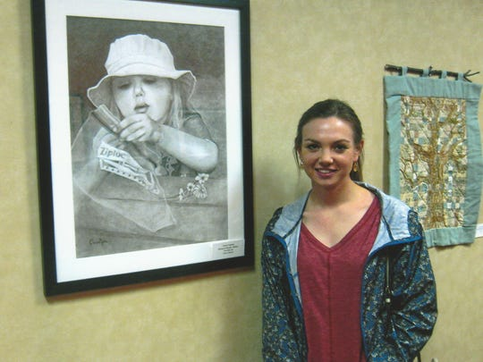 CharlesAnn Freeman, the daughter of Christy and Glen Freeman, of Abilene, views a drawing that her grandmother, Carolyn Freeman, made of her as a child. The drawing is on exhibit in the Abilene ISD administration building.