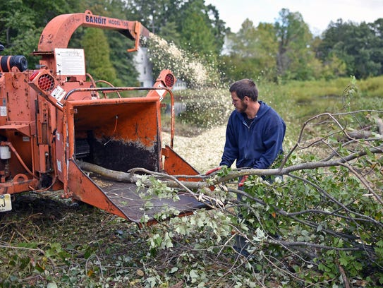 Rich Grierson feeds a tree limb into a wood chipper