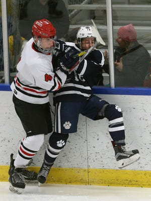 Penfield's Jack Schlfike (4) gets a check on Pittsford's Zach Gmerek (18) along the boards.